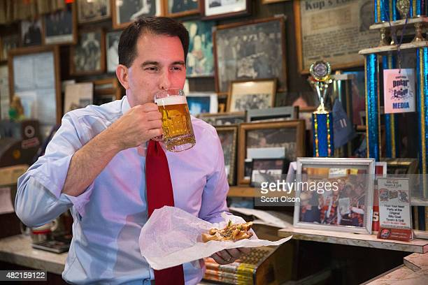 Republican presidential hopeful Wisconsin Governor Scott Walker washes down a 'cheezborger' with a Schlitz beer at the famed Billy Goat Tavern during...