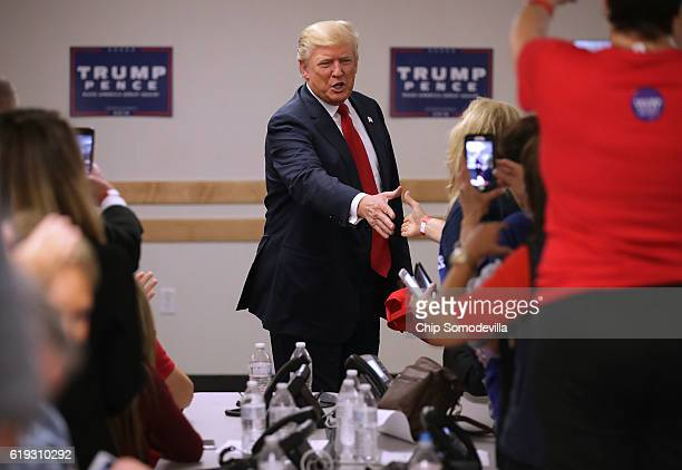 Republican presidential nominee Donald Trump greets volunteers at a campaign phone bank before a rally at the Bank of Colorado Arena on the campus of...