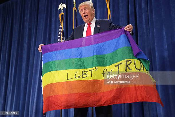 Republican presidential nominee Donald Trump holds an LGBT rainbow flag given to him by supporter Max Nowak during a campaign rally at the Bank of...