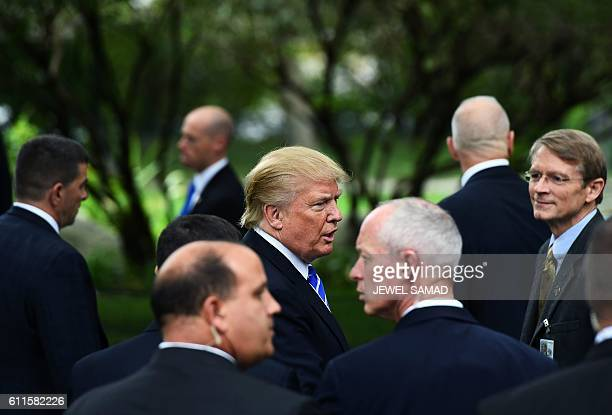 US Republican presidential nominee Donald Trump is surrounded by members of the Secret Service as he visits the tomb of former US President Gerald...