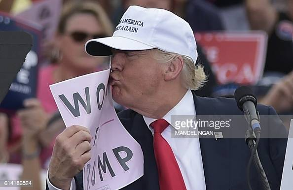 Republican presidential nominee Donald Trump kisses a 'Women for Trump' placard during a rally at the Lakeland Linder Regional Airport in Lakeland...