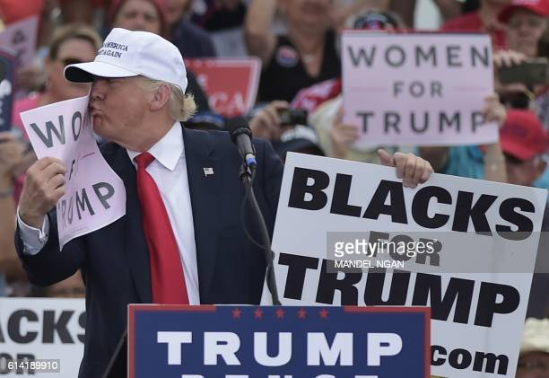 TOPSHOT Republican presidential nominee Donald Trump kisses a 'Women for Trump' placard during a rally at the Lakeland Linder Regional Airport in...