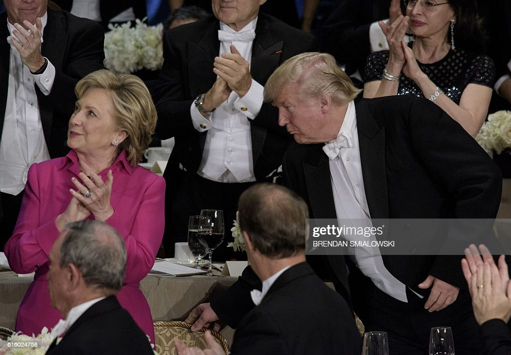 TOPSHOT - Republican presidential nominee Donald Trump moves Democratic presidential nominee Hillary Clinton's chair during the Alfred E. Smith Memorial Foundation Dinner at Waldorf Astoria October 20, 2016 in New York, New York. / AFP / Brendan Smialowski
