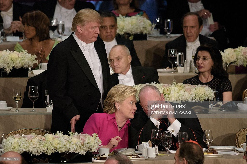 TOPSHOT - Republican presidential nominee Donald Trump pats Democratic presidential nominee Hillary Clinton on the back as she speaks with Timothy Cardinal Dolan, Archbishop of New York, during the Alfred E. Smith Memorial Foundation Dinner at Waldorf Astoria October 20, 2016 in New York, New York. / AFP / Brendan Smialowski