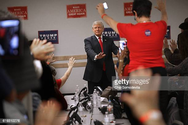 Republican presidential nominee Donald Trump reaches out and prays with volunteers at a campaign phone bank before a rally at the Bank of Colorado...