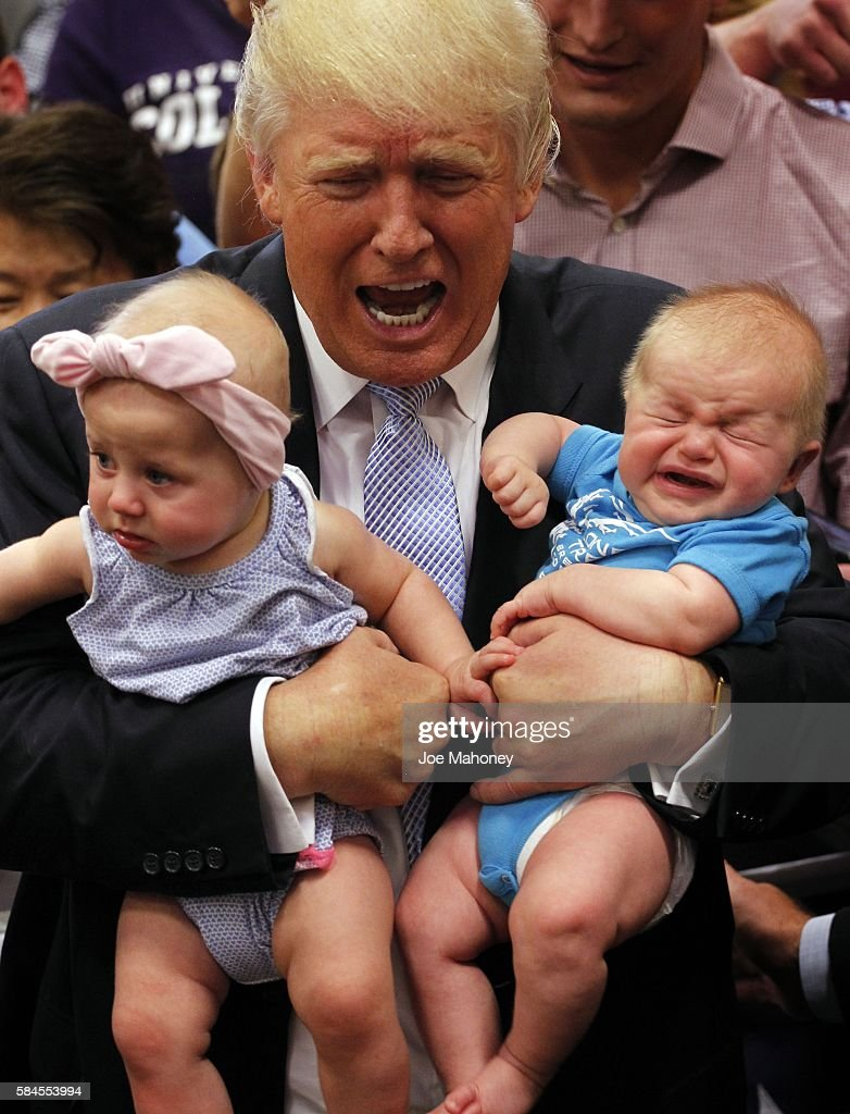 Republican presidential nominee Donald Trump reacts to the cries of three-month-old Kellen Campbell, of Denver, right, while holding six-month-old Evelyn Keane, of Castel Rock, Colo., after Trump's speech at the Gallogly Event Center on the campus of the University of Colorado on July 29, 2016 in Colorado Springs, Colorado.