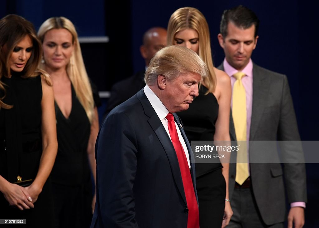TOPSHOT - Republican presidential nominee Donald Trump (C) walks off the stage surrounded his wife Melania Trump (L), his son Donald Jr (R) and other memebers of his family after the final presidential debate at the Thomas & Mack Center on the campus of the University of Las Vegas in Las Vegas, Nevada on October 19, 2016. / AFP / Robyn Beck