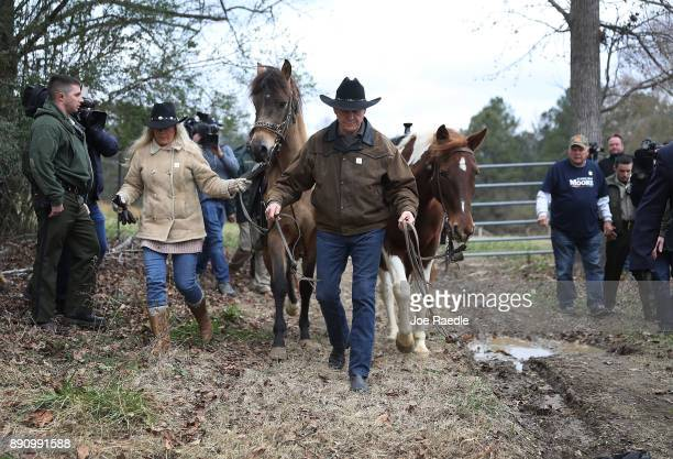Republican Senatorial candidate Roy Moore and his wife Kayla Moore prepare to ride their horses after casting their votes at the polling location...