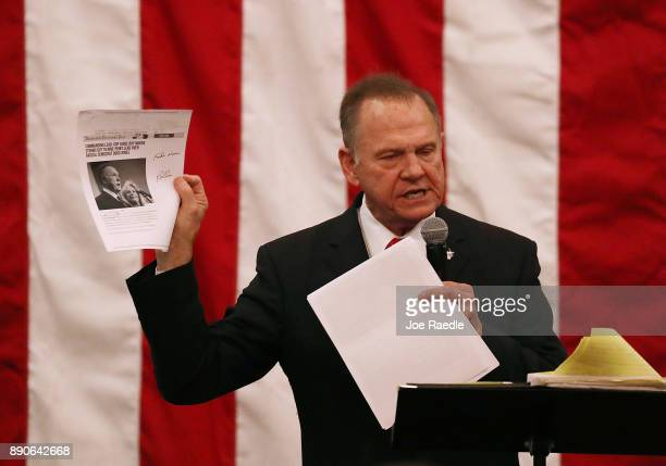 Republican Senatorial candidate Roy Moore holds up a news story that shows his opponent is up in a poll as he speaks during a campaign event at...