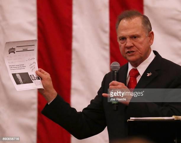 Republican Senatorial candidate Roy Moore holds up a print out of a news story as he speaks during a campaign event at Jordan's Activity Barn on...