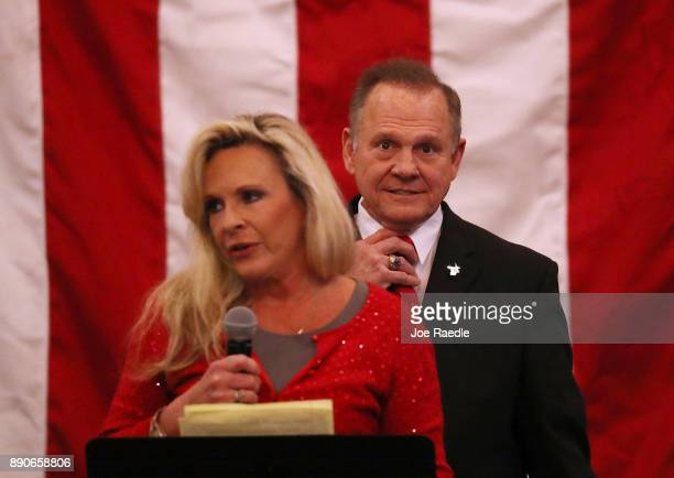 Republican Senatorial candidate Roy Moore stands behind his wife Kayla Moore as she speaks during a campaign event at Jordan's Activity Barn on...