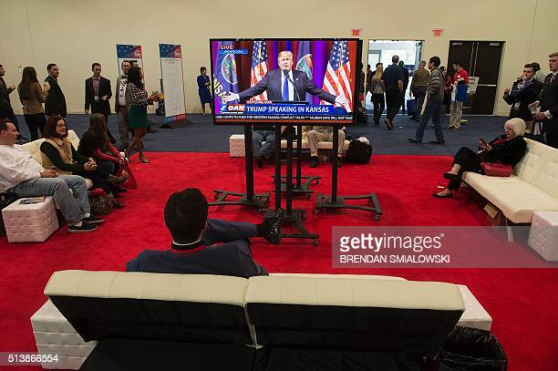 TOPSHOT Republican US Presidential hopeful Donald Trump is seen on a screen as he speaks from a rally in Kansas during the American Conservative...