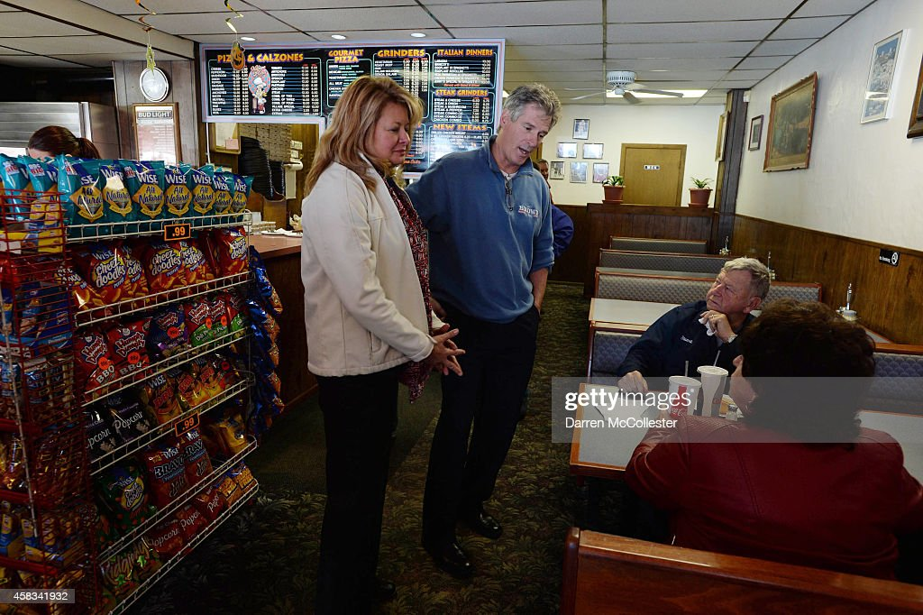 Republican U.S. Senate candidate <a gi-track='captionPersonalityLinkClicked' href=/galleries/search?phrase=Scott+Brown+-+Politician&family=editorial&specificpeople=6698204 ng-click='$event.stopPropagation()'>Scott Brown</a> (2nd L) and wife Gail talk with Stuart and Joanne Stone at Village Pizza of Newport during a campaign stop November 3, 2014 in Newport, New Hampshire. Brown is in a tight race with incumbent U.S. Senator Jeanne Shaheen (D-NH) going into election day on November 4.