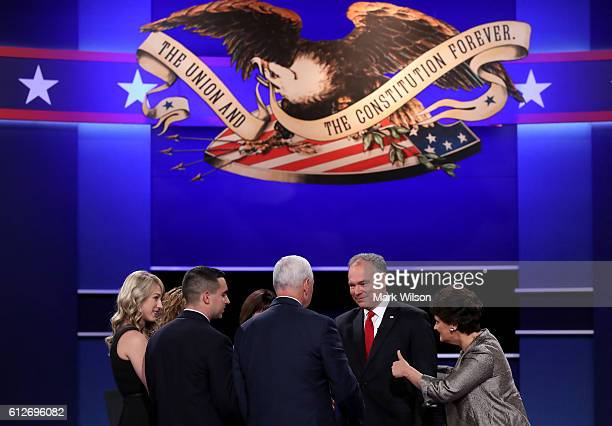 Republican vice presidential nominee Mike Pence and Democratic vice presidential nominee Tim Kaine shake hands on stage surrounded by family members...