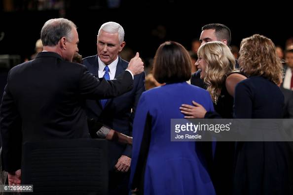 Republican vice presidential nominee Mike Pence and Democratic vice presidential nominee Tim Kaine meet on stage surrounded by family members...
