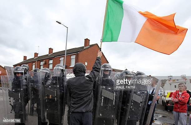 A Republicans holds an Irish Flag as he stands next to a line of police during clashes in the Oldpark area of north Belfast northern Ireland on...