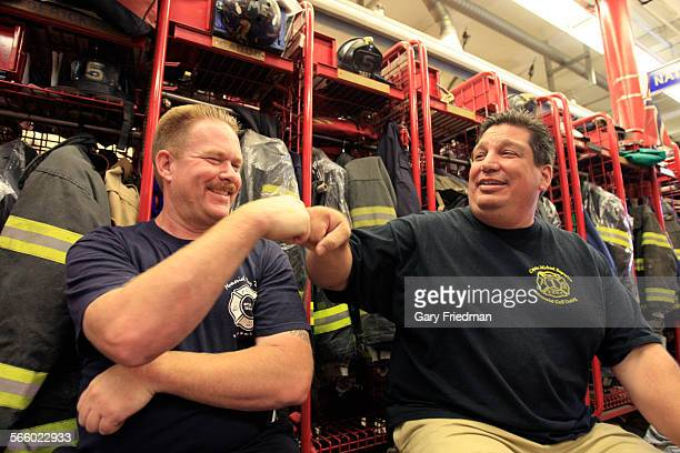 Rescue 5 firefighter Joey Esposito touches knuckles with fellow firefighter John Leahy in the Rescue 5/Engine 160 firehouse on July 5 2011 Joey is...