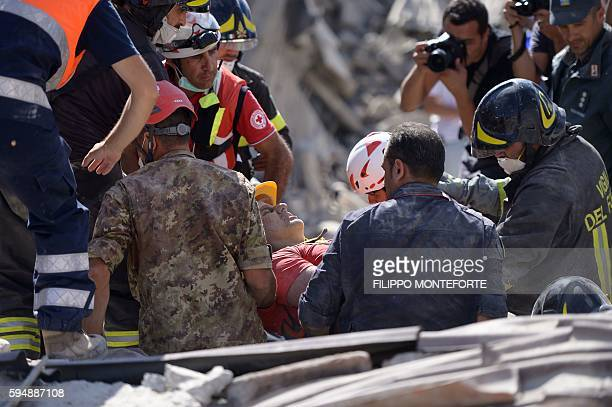 Rescue and emergency services personnel carry out search and rescue operations work in Amatrice on August 24 2016 after a powerful earthquake rocked...