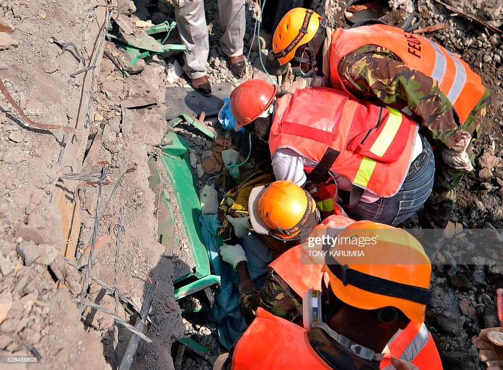 Rescue and medical personnel try to free a woman who discovered alive May 5, 2016 after being trapped for six-days in the rubble of a residential house that collapsed during torrential rain in Kenyan capital, Nairobi's low-income subusrb of Huruma. The woman was pulled out hours after being located on May 5, 2016 morning by rescuers who gave her oxygen while they continued efforts to extract her from the ruins of the six-storey building. / AFP / TONY