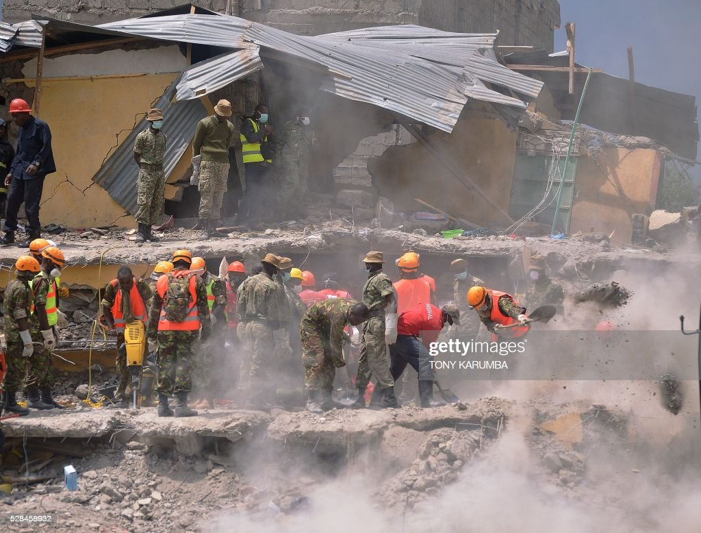 Rescue and medical personnel try to free a woman (unseen) who discovered alive May 5, 2016 in Nairobi after being trapped for six-days in the rubble of a residential house that collapsed during torrential rain in Kenyan capital, Nairobi's low-income subusrb of Huruma. The woman was pulled out hours after being located on May 5, 2016 morning by rescuers who gave her oxygen while they continued efforts to extract her from the ruins of the six-storey building. / AFP / TONY