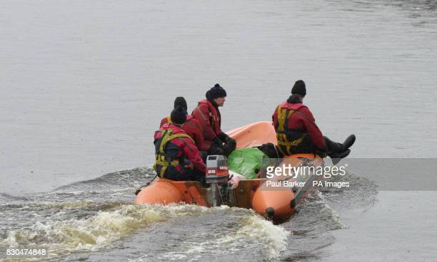 A rescue boats carries a body found during the search for two girls who were swept away while 'river walking' in a swollen beck during a school trip...