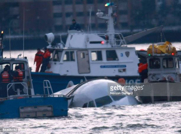 Rescue boats float near a US Airways plane floating in the water after crashing into the Hudson River in the afternoon on January 15 2009 in New York...