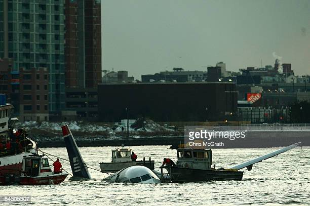 Rescue boats float next to a US Airways plane floating in the water after crashing into the Hudson River in the afternoon on January 15 2009 in New...