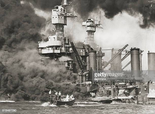 Rescue boats move in on the battleships USS West Virginia and USS Tennessee which sit low in the water and burn after the Japanese surprise attack on...