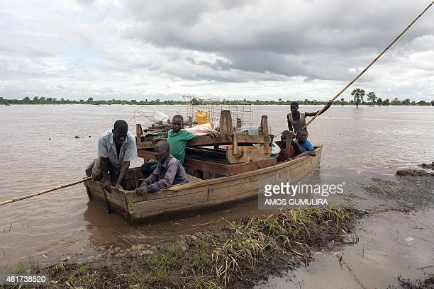 A rescue canoe transporting people arrives at the village of Chambuluka on the bank of the flooded Ruo river in the area of Traditional Authority...