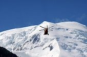 A rescue crew of the Securite Civile flies over the Mont Blanc massif in an helicopter on July 12 2012 in Chamonix in the French Alps to the Mont...