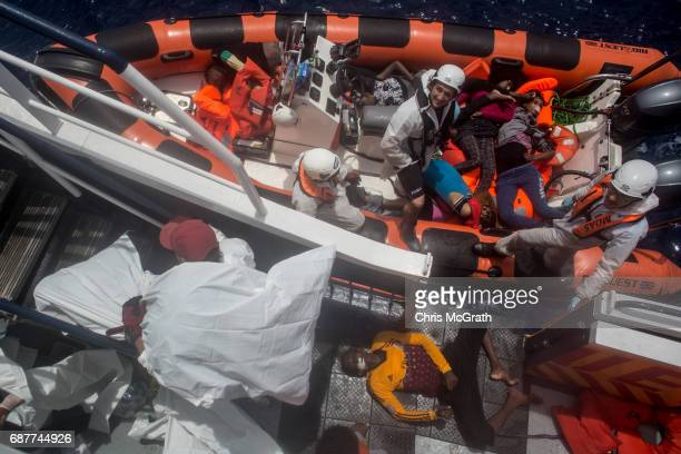 Rescue crews and medical staff of the Migrant Offshore Aid Station 'Phoenix' vessel unload the bodies of people that drowned at sea after a wooden...