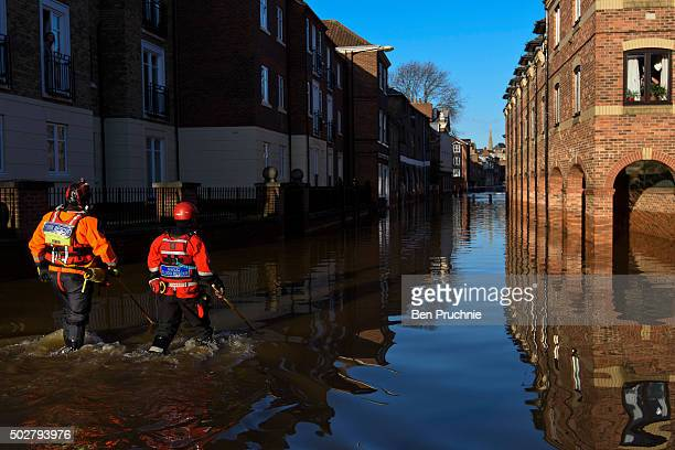 Rescue crews use poles to check the depth of the flood water in Skeldergate on December 29 2015 in York England Heavy rain over the Christmas period...