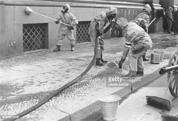Rescue exercises before a gas and aerial attack After a bomb attack the decontamination squad cleans the street Vintage property of ullstein bild