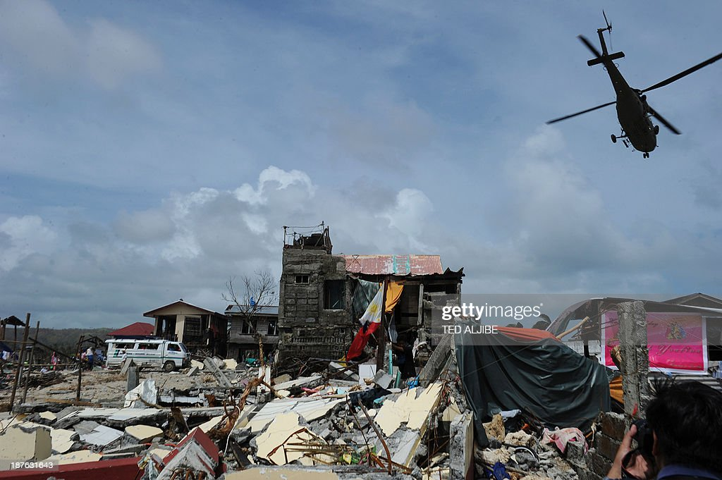 A rescue helicopter flies past a tattered national flag (C) and destroyed houses in the town of Hernani in Eastern Samar province, central Philippines on November 11, 2013, four days after Typhoon Haiyan hit the country. Philippines rescue workers struggled to bring aid to famished and destitute survivors on November 11 after the super typhoon that may have killed more than 10,000 people, in what is feared to be the country's worst natural disaster.