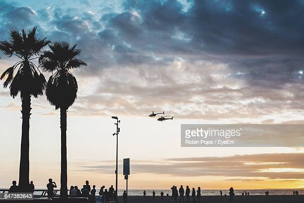 Rescue Helicopter Hovering Over Sea At Sunset