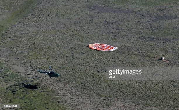 A rescue helicopter of Russian space agency Roskosmos approaches the Russian Soyuz space capsule with US astronaut Tom Marshburn Canadian spaceman...