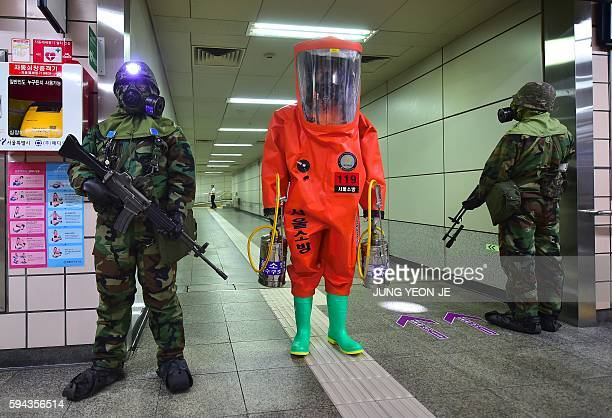 TOPSHOT A rescue member in full protective gear stands amongst South Korean soldiers wearing gas masks during an antiterror drill on the sidelines of...