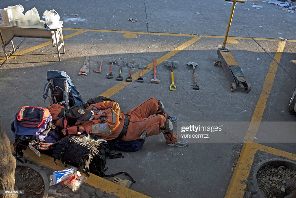 A rescue member takes a break after working looking for victims at the headquarters of state-owned Mexican oil giant Pemex in Mexico City on February 1, 2013, following a blast inside the building which leaves up to now 32 dead and 100 injured. AFP PHOTO/ YURI CORTEZ