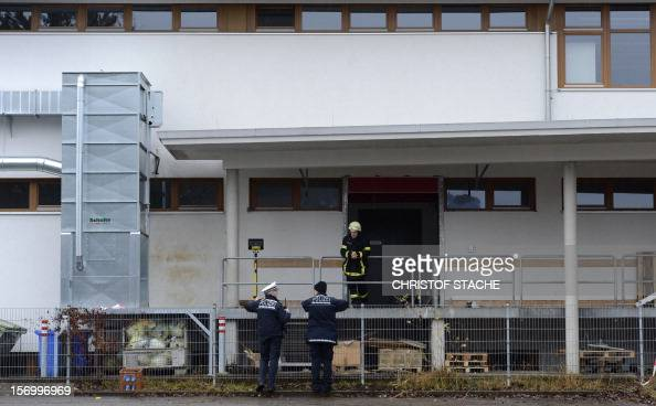 Rescue officers stand in front of an entrance to a workshop for handicapped people in TitiseeNeustadt southern Germany on November 27 2012 A fire...