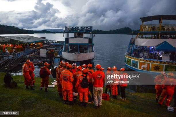 Rescue officials gather to take part in a search for survivors after the tourist boat Almirante sank in the Reservoir of Penol in Guatape...