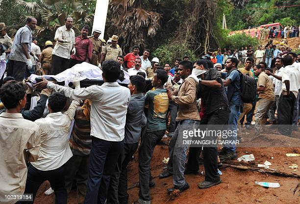 Rescue personnel and volunteers carry a victims body on a stretcher at the crash site of an Air India Boeing 737800 aircraft which crashed upon...