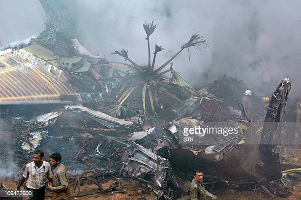 Rescue personnel are seen near the smouldering wreckage of an Air India Boeing 737800 aircraft which crashed upon landing in Mangalore on May 22 2010...