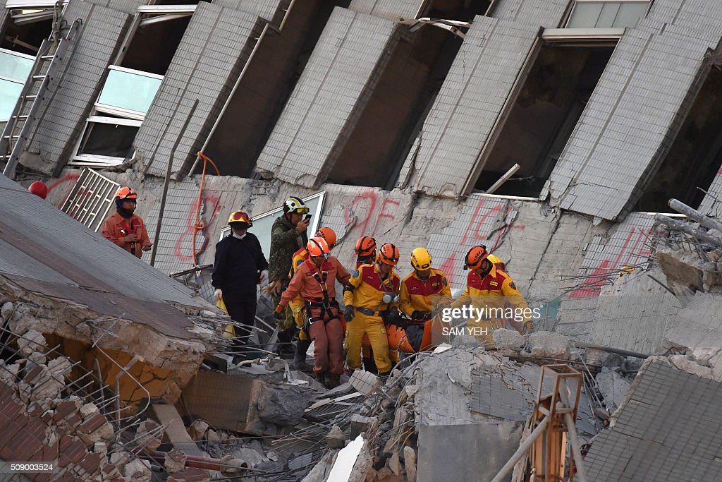 Rescue personnel bring down a Vietnamese national, identified as 28-year old Chen Mei-Jih, to safety after she was extracted from the rubble at the Wei-Kuan complex which collapsed in the 6.4 magnitude earthquake, in the southern Taiwanese city of Tainan on February 8, 2016. Two survivors were on February 8 rescued from the rubble of an apartment complex in Taiwan felled by an earthquake, after being trapped for more than 50 hours. AFP PHOTO / Sam Yeh / AFP / SAM YEH