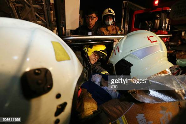 Rescue personnel carry a baby at the site of a collapsed building in the southern Taiwanese city of Tainan following a strong 64magnitude earthquake...