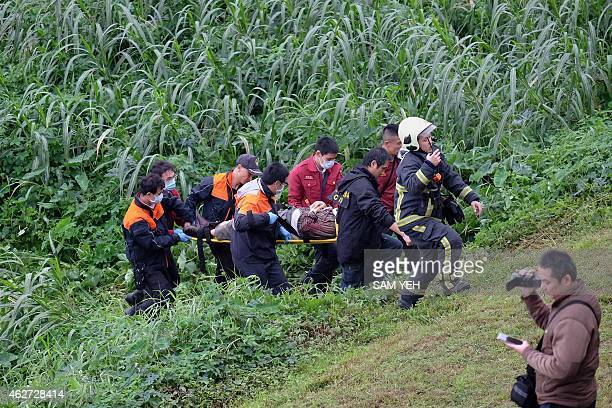 Rescue personnel carry a passenger from a TransAsia ATR 72600 turboprop plane that crashlanded into a river outside Taiwan's capital Taipei on a...