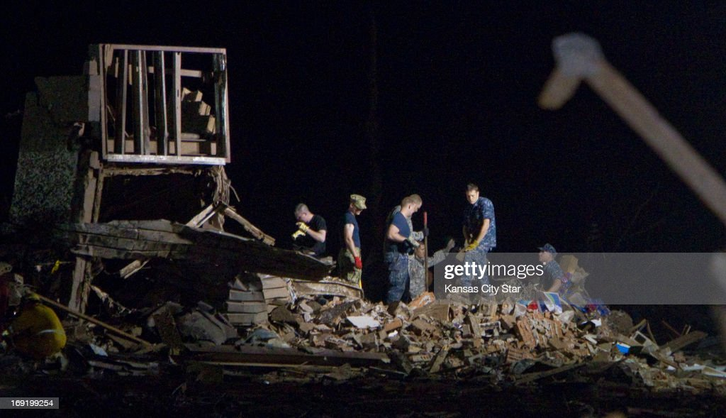 Rescue personnel comb through the pile of rubble that was once Plaza Towers Elementary School, as emergency crews continued searching for children in the early morning hours on Tuesday, May 21, 2013, in Moore, Oklahoma, after a tornado ripped through part of the town.