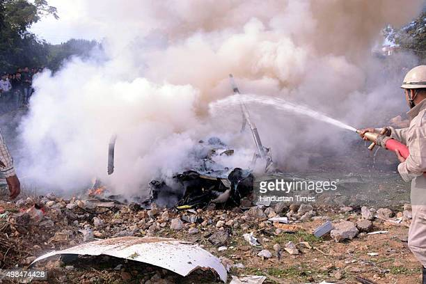 Rescue personnel douse the smoldering wreckage of crashed helicopter at Katra on November 23 2015 in Jammu India Seven Vaishno Devibound pilgrims...