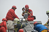TOPSHOT Rescue personnel help a young victim at the site of a collapsed building in the southern Taiwanese city of Tainan following a strong...