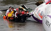 Rescue personnel help passengers as they wait to be transported to land from the wreckage of a TransAsia ATR 72600 turboprop plane that crashlanded...