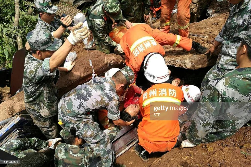 Rescue personnel lift out an injured man after a landslide at Pianpo village in China's southwest Guizhou province on July 1, 2016. Heavy rain caused a landslide in southwestern China on July 1 that killed at least six and left 17 others missing, local officials said. / AFP / STR / China OUT